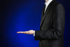 Businessman and gesture topic: a man in a black suit and white shirt showing gestures with hands on a dark blue background in stud Royalty Free Stock Image