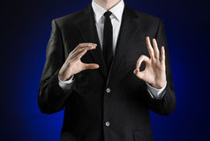 Businessman and gesture topic: a man in a black suit and white shirt showing gestures with hands on a dark blue background in stud Royalty Free Stock Photography