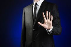 Businessman and gesture topic: a man in a black suit and white shirt showing gestures with hands palm against the dark blue isolat Royalty Free Stock Photography
