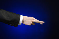 Businessman and gesture topic: a man in a black suit and white shirt showing hand gesture on an isolated dark blue background in s. Businessman and gesture topic Stock Photography