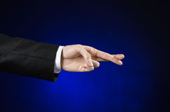 Businessman and gesture topic: a man in a black suit and white shirt showing hand gesture on an isolated dark blue background in s Stock Photos