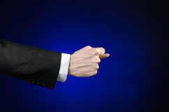 Businessman and gesture topic: a man in a black suit and white shirt showing hand gesture on an isolated dark blue background in s. Businessman and gesture topic Royalty Free Stock Image
