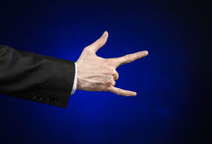 Businessman and gesture topic: a man in a black suit and white shirt showing hand gesture on an isolated dark blue background in s Royalty Free Stock Images