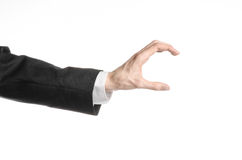 Businessman and gesture topic: a man in a black suit and white shirt showing hand gesture on an isolated white background in studi. Businessman and gesture topic Royalty Free Stock Images