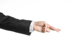 Businessman and gesture topic: a man in a black suit and white shirt showing hand gesture on an isolated white background in studi Royalty Free Stock Images