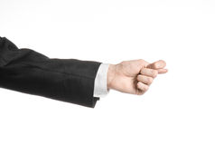 Businessman and gesture topic: a man in a black suit and white shirt showing hand gesture on an isolated white background in studi. Businessman and gesture topic Stock Image