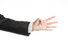 Businessman and gesture topic: a man in a black suit and white shirt showing hand gesture on an isolated white background in studi Royalty Free Stock Photos