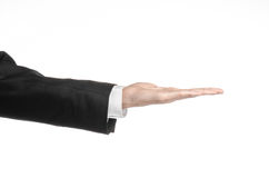 Businessman and gesture topic: a man in a black suit and white shirt showing hand gesture on an isolated white background in studi Stock Images