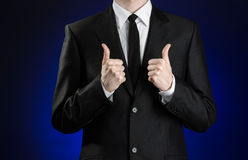 Businessman and gesture topic: a man in a black suit and white shirt showing hand gestures a thumbs-up on a dark blue background i Royalty Free Stock Photography
