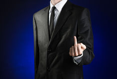 Businessman and gesture topic: a man in a black suit and white shirt showing middle finger gesture on a dark blue background in st Royalty Free Stock Photography