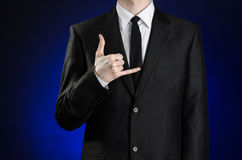 Businessman and gesture topic: a man in a black suit and white shirt showing sign a telephone hands on a dark blue background in s Stock Photo