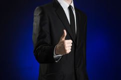 Businessman and gesture topic: a man in a black suit and white shirt showing a thumbs up hand on a dark blue background in studio Stock Photography