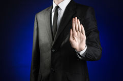 Businessman and gesture topic: a man in a black suit and white shirt shows a hand stop sign on a dark blue background in studio is Stock Photography