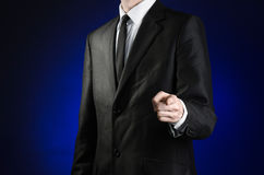 Businessman and gesture topic: a man in a black suit and white shirt shows his hand forward on a dark blue background in studio is Stock Photos