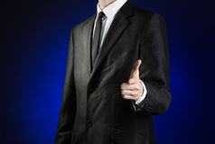 Businessman and gesture topic: a man in a black suit and white shirt shows his hand forward on a dark blue background in studio is Royalty Free Stock Photo