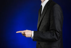 Businessman and gesture topic: a man in a black suit and white shirt shows his hand forward on a dark blue background in studio is Stock Photo