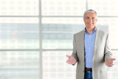 Businessman Gesturing with Both Hands. Closeup of a smiling middle aged businessman gesturing with both hand. Man is standing in front of a large modern office Stock Images