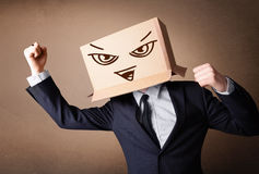 Businessman gesturing with a cardboard box on his head with evil. Businessman standing and gesturing with a cardboard box on his head with evil face Stock Photos