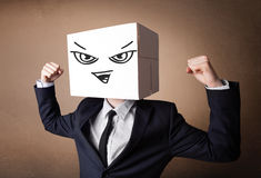 Businessman gesturing with a cardboard box on his head with evil Stock Image