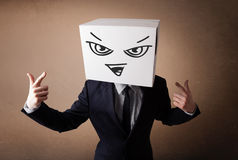 Businessman gesturing with a cardboard box on his head with evil Royalty Free Stock Images