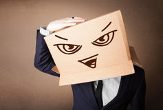 Businessman gesturing with a cardboard box on his head with evil Royalty Free Stock Photos