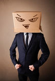 Businessman gesturing with a cardboard box on his head with evil Royalty Free Stock Photo