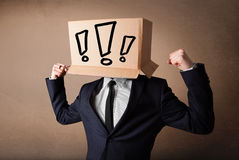 Businessman gesturing with a cardboard box on his head with excl Stock Images