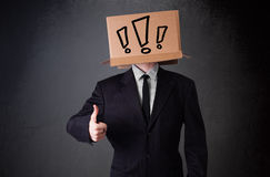 Businessman gesturing with a cardboard box on his head with excl Stock Photos