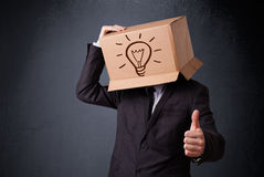 Businessman gesturing with a cardboard box on his head with ligh Stock Photos