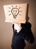 Businessman gesturing with a cardboard box on his head with ligh Royalty Free Stock Photo