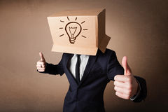 Businessman gesturing with a cardboard box on his head with ligh Stock Image