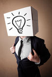 Businessman gesturing with a cardboard box on his head with ligh Royalty Free Stock Photos