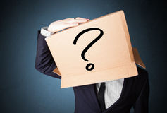 Businessman gesturing with a cardboard box on his head with ques Stock Images