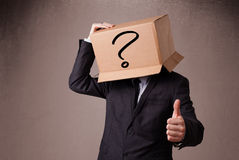 Businessman gesturing with a cardboard box on his head with ques Royalty Free Stock Photo