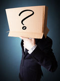 Businessman gesturing with a cardboard box on his head with ques Royalty Free Stock Images