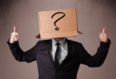 Businessman gesturing with a cardboard box on his head with ques Stock Photography