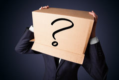 Businessman gesturing with a cardboard box on his head with ques Stock Photo
