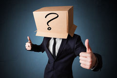 Businessman gesturing with a cardboard box on his head with ques Royalty Free Stock Photography
