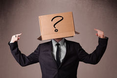 Businessman gesturing with a cardboard box on his head with ques Royalty Free Stock Photos