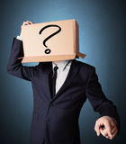 Businessman gesturing with a cardboard box on his head with ques Stock Photos