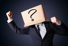 Businessman gesturing with a cardboard box on his head with ques Royalty Free Stock Image