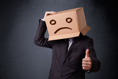 Businessman gesturing with cardboard box on his head with sad fa Stock Photos