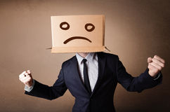 Businessman gesturing with cardboard box on his head with sad fa Stock Photo