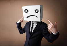Businessman gesturing with cardboard box on his head with sad fa Royalty Free Stock Photo