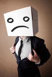 Businessman gesturing with cardboard box on his head with sad fa Stock Photos