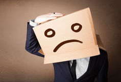 Businessman gesturing with cardboard box on his head with sad fa. Businessman standing and gesturing with a cardboard box on his head with sad face Royalty Free Stock Photography
