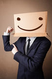 Businessman gesturing with a cardboard box on his head with smil Stock Photos