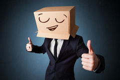 Businessman gesturing with a cardboard box on his head with smil Royalty Free Stock Photo