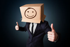 Businessman gesturing with a cardboard box on his head with smil Royalty Free Stock Image