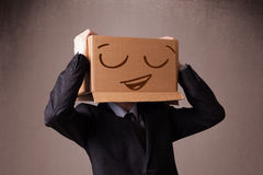 Businessman gesturing with a cardboard box on his head with smil Royalty Free Stock Images